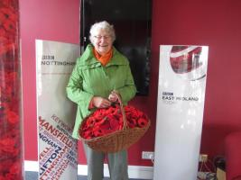 Bestwood Village WI President Brenda Langsdale delivers a basket of crocheted poppies to BBC Radio Nottingham.