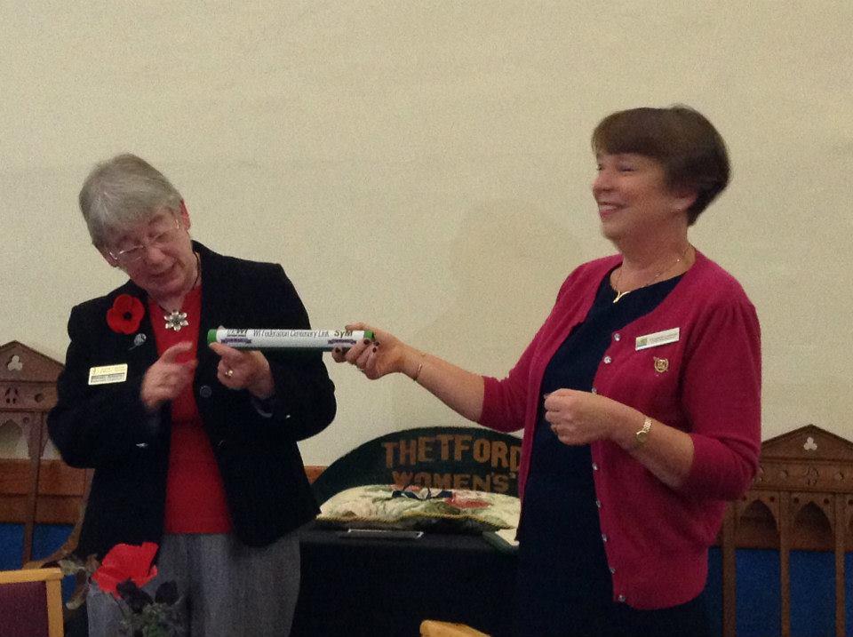 Norfolk Federation Chairman Wendy Adams passes the baton to Suffolk West Federation Chairman Elizabeth Lansman.