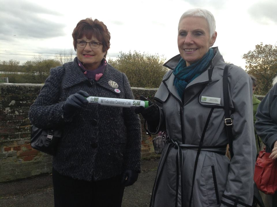 Pat Pratley, Essex Federation Chairman, receives the Baton from Jane Collier, Chairman of the East Suffolk Federation, at Cattawade Bridge.